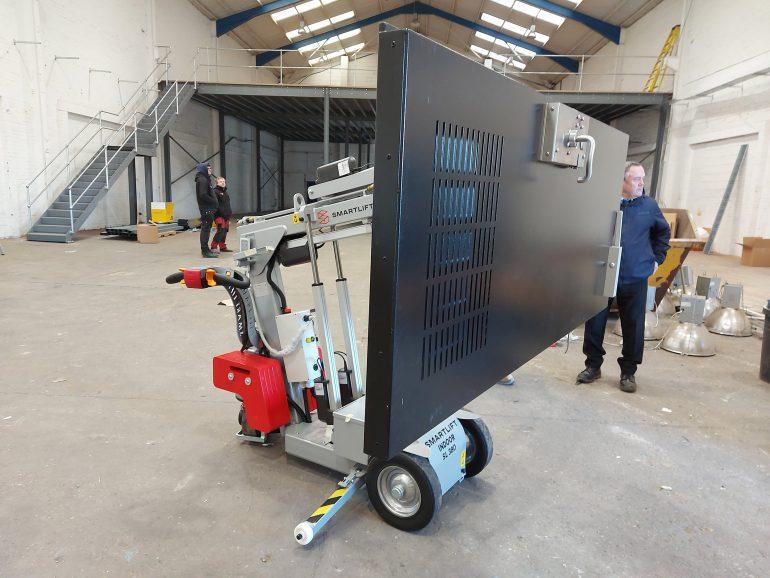 A Smartlift lifting a heavy steel security door.